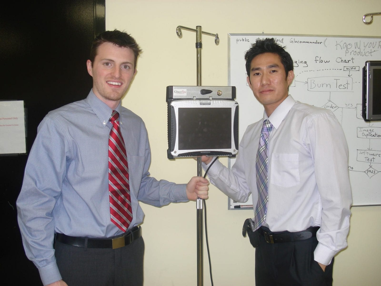 Two men standing next to an IV stand with the Glucommander tablet on the IV pole.